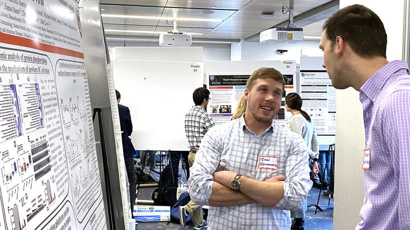 Two men from lab group stand in front of lab poster at HUROS Fair 2019