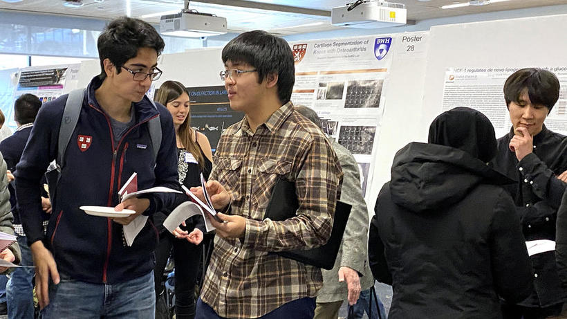 Two male undergraduates discuss lab choices at HUROS Fair 2019