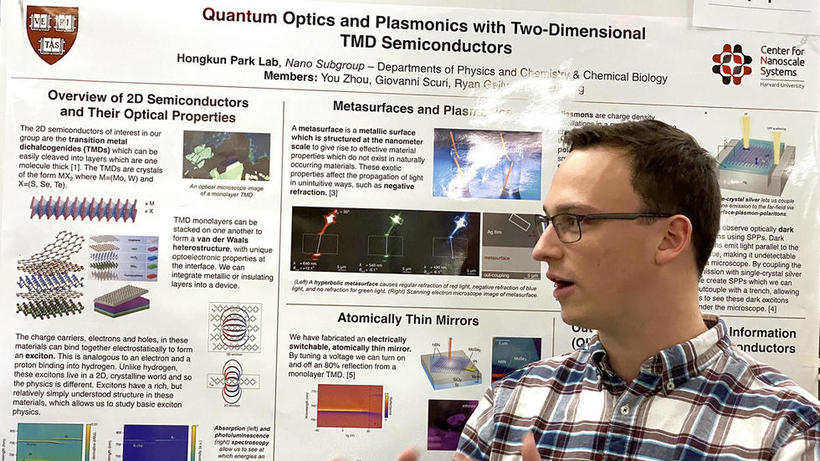 Male lab representative stands in front of Quantum Optics poster at HUROS 2019 fair