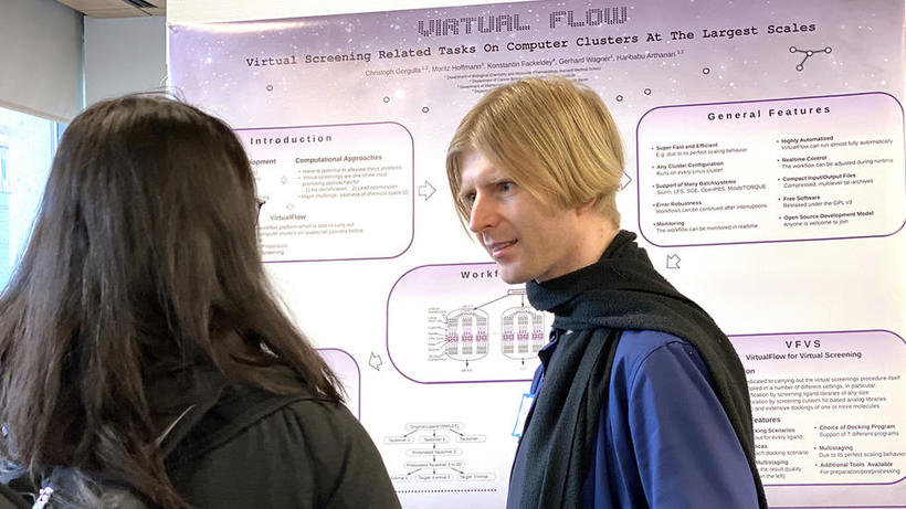 Male lab representative stands in front of Virtual Flow poster at HUROS 2019 fair