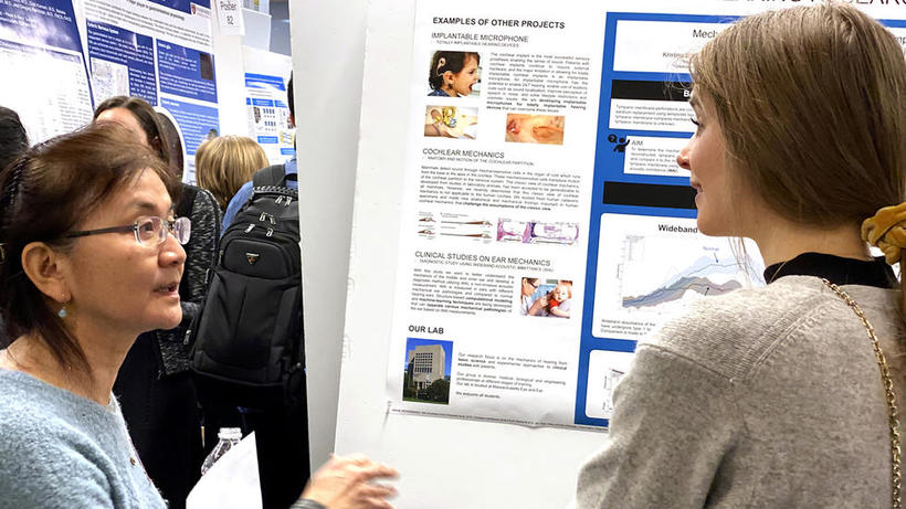 Female lab representative for hearing research discusses poster with female student at HUROS 2019 fair