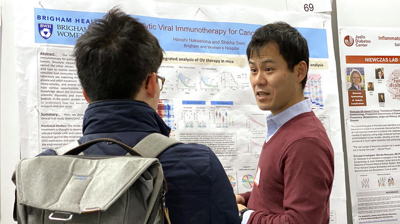 Male lab group member stands in front of poster and discusses OV therapy in mice with male student at HUROS Fair 2019