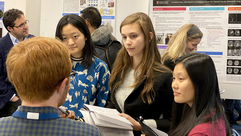 Three female students discuss lab poster at HUROS 2019 fair