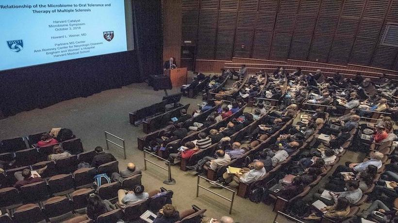 Photo of attendees watching a presentation at the Microbiome in Human Disease Symposium.