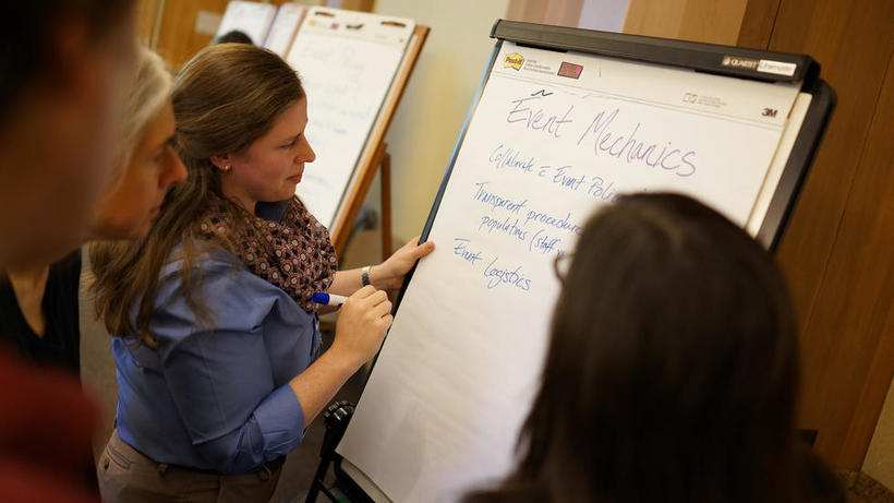 A library staff member annotates a clipboard as part of an active learning exercise.