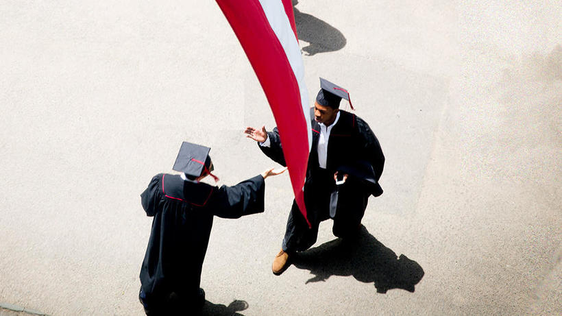 (photo of two capped and gowned graduates reaching out to shake hands)