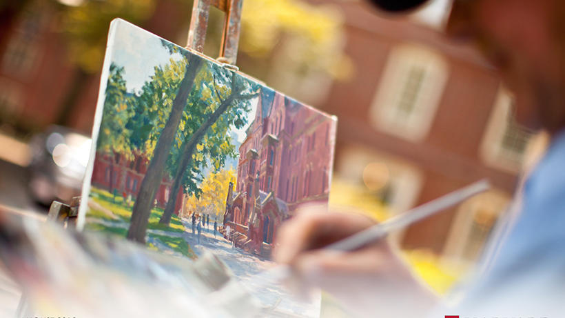(Photo of someone painting at an easel in Harvard Yard)