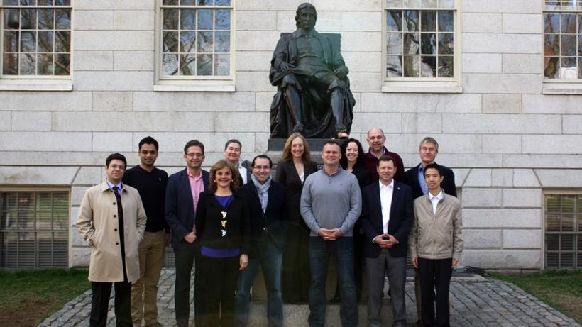 2014-2015 Class of WCFIA Fellows in front of the statue of John Harvard.