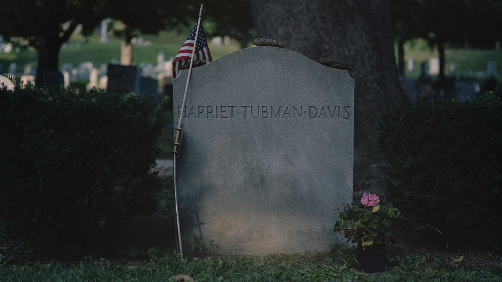 Photo of Harriet Tubman's gravestone, with small American flag and a few pine cones placed on top