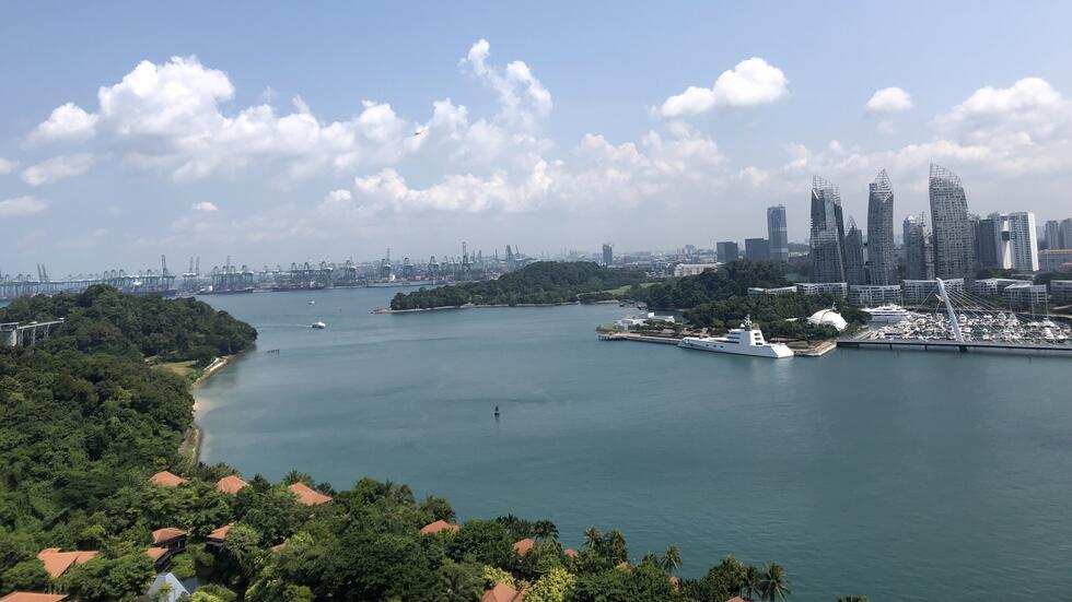 A body of water runs through the center of the image. To the left, a coastline covered in greenery looks out on the skyline of singapore, bristling with skyscrapers.