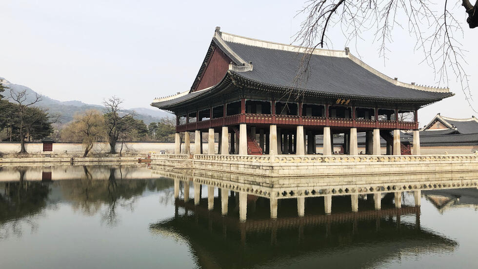 Inside an expansive Korean palace complex, a pagoda-like structure stands on stilts in the middle of a manmade pond.