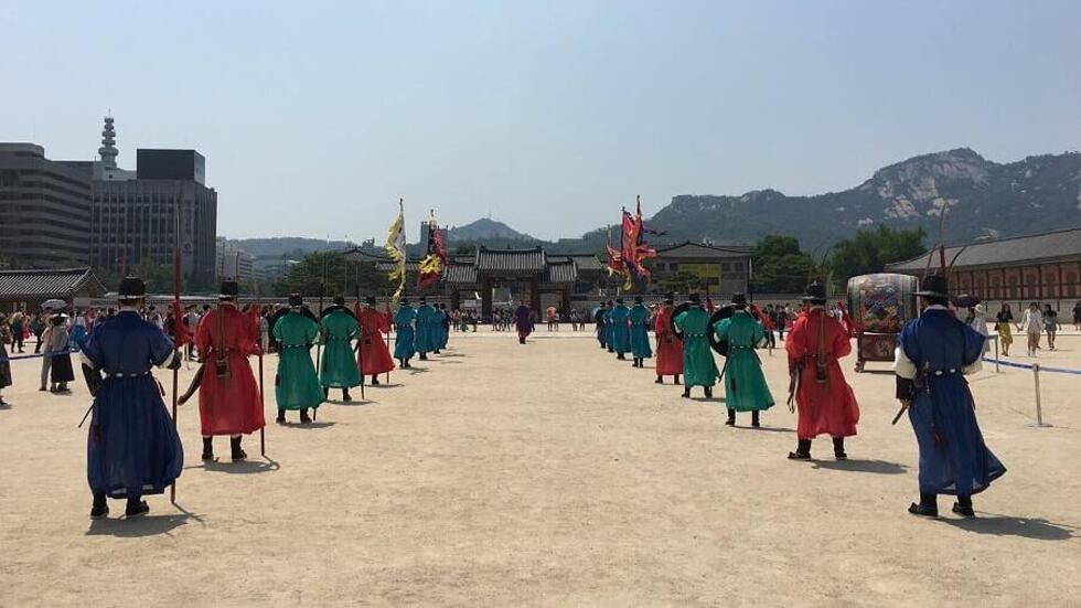 Two lines of men in blue, red, and green traditional Korean court dress proceed toward a palace gate.