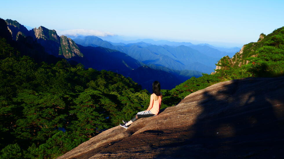 The small figure of a woman sits on a slope overlooking an expansive view of a mountain range, with blue mountains stretching off to the skyline.