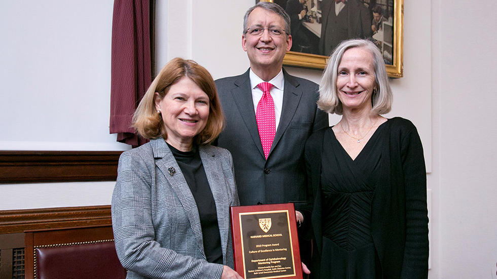 pat d'amore, david hunter, and anne levy pose in front of award