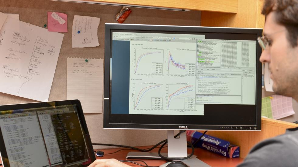A researcher studies data on two monitors