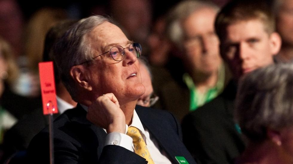"David Koch listens to Republican presidential hopeful Mitt Romney addressing the ""Defending The American Dream Summit"" organized by Americans for Prosperity in Washington, DC on November 4, 2011."