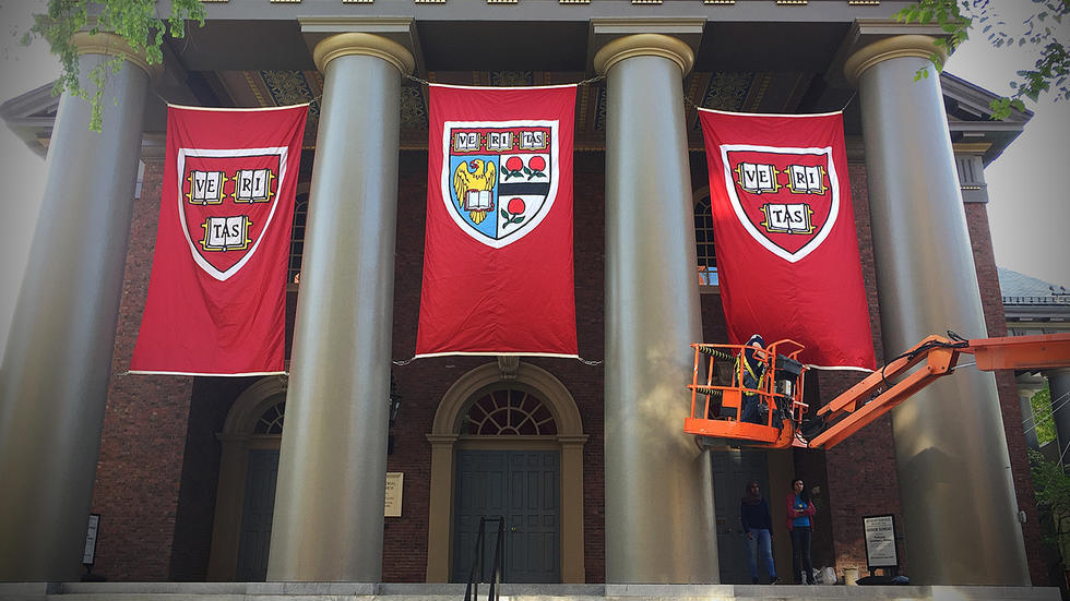 Crews hang banners on Memorial Church in preparation of Commencement