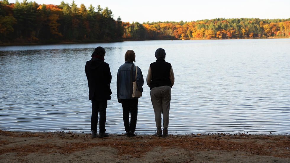 Professor Stephanie Paulsell and two students stand on the shore of Walden Pond