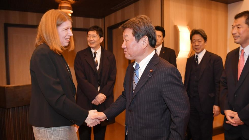 Director Christina Davis shakes hands with Foreign Minister Toshimitsu Motegi