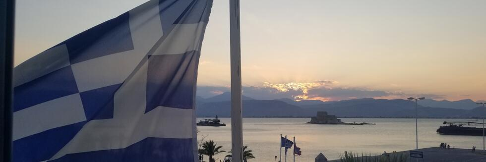 Bourtzi view with the sun setting on a summer evening and the Greek flag on the foreground.