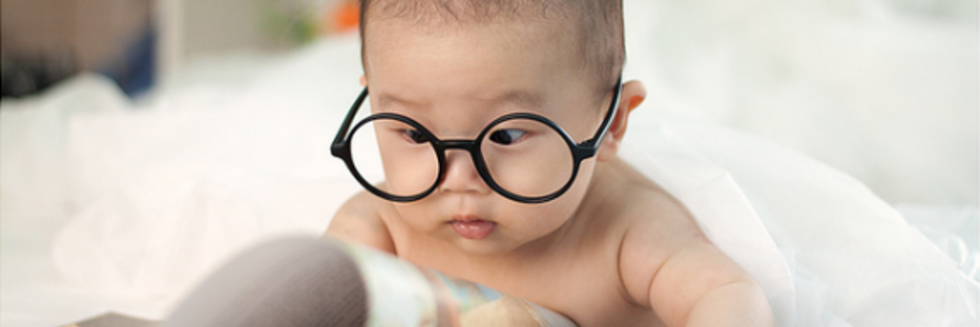Baby with glasses reading