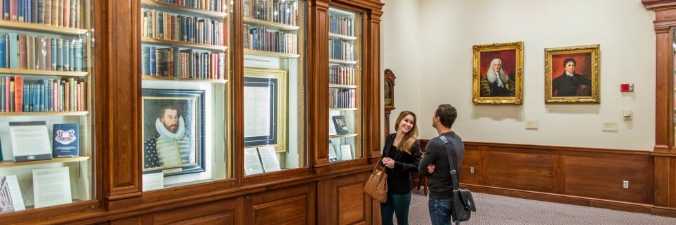 Color image of a man and woman standing in the Library's Caspersen Room in front of a series of built in bookshelves with books and paintings.