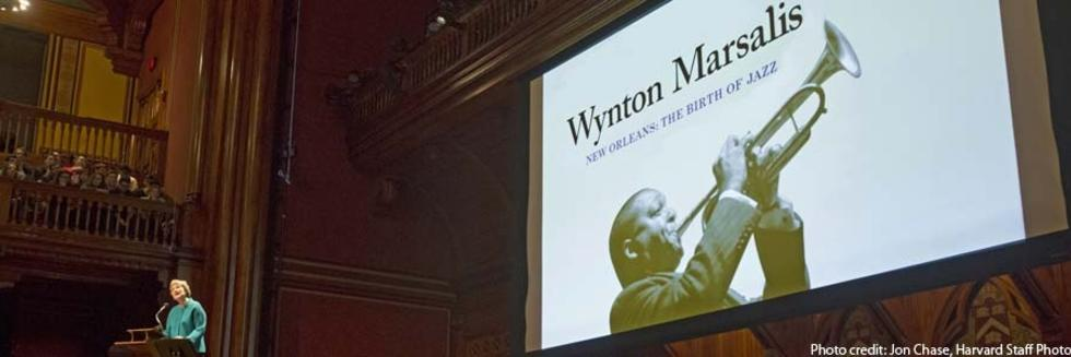 President Faust speaking in Sanders Theater, projected image of Wynton Marsalis