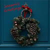 "Christmas wreath with pinecones hanging from a red ribbon on a knocker of a blue door. ""Season's Greetings"" message is also added, and photo credit to Erwan Hesry, Unsplash."