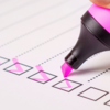 Image of a pink highlighter checking off boxes