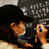 woman in dark hat and mask writing on a chalkboard