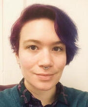 Nonbinary person with purple hair smiles at the camera.